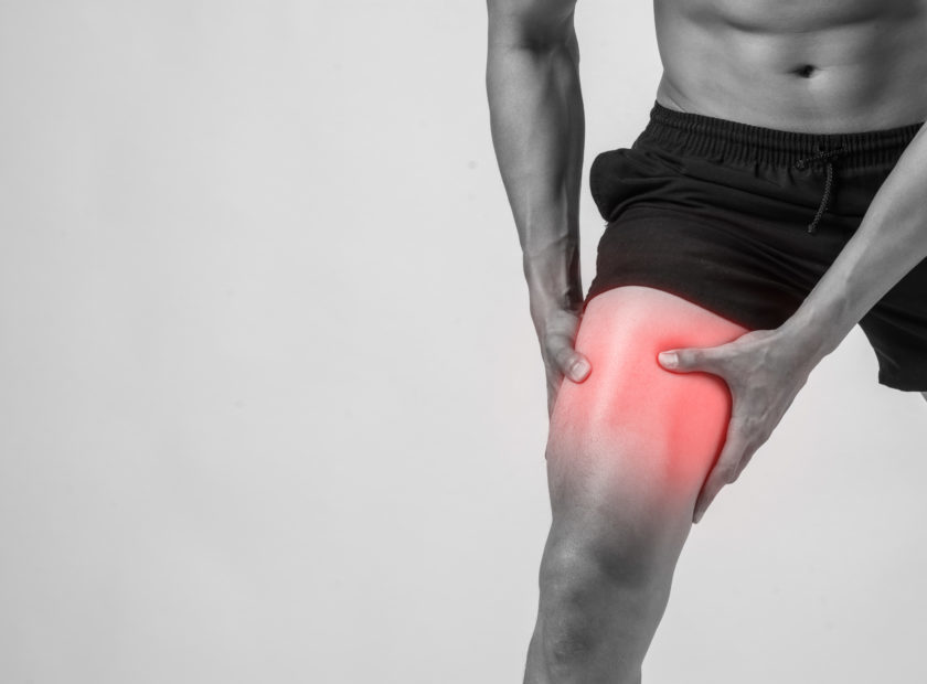 Young sport man with strong athletic legs holding knee with his